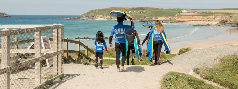 Group Walking Down For Surf Lesson On Gwithian